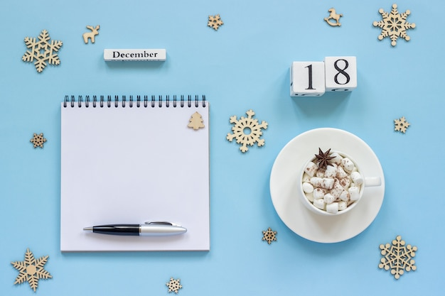 Composición de invierno. calendario de madera 18 de diciembre taza de cacao con malvavisco y anís estrellado, libreta abierta vacía con bolígrafo y copo de nieve sobre fondo azul. vista superior concepto de maqueta plana endecha