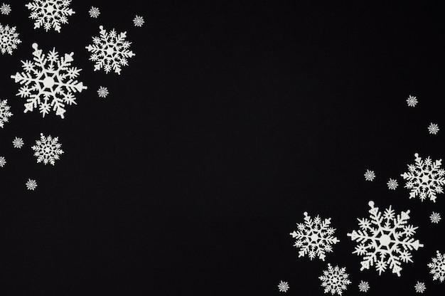 Composición de invierno hecha de copos de nieve sobre fondo negro con espacio de copia, tarjeta de navidad, endecha plana, vista superior
