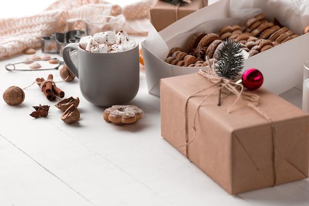 Composición de invierno. regalos y taza con malvavisco