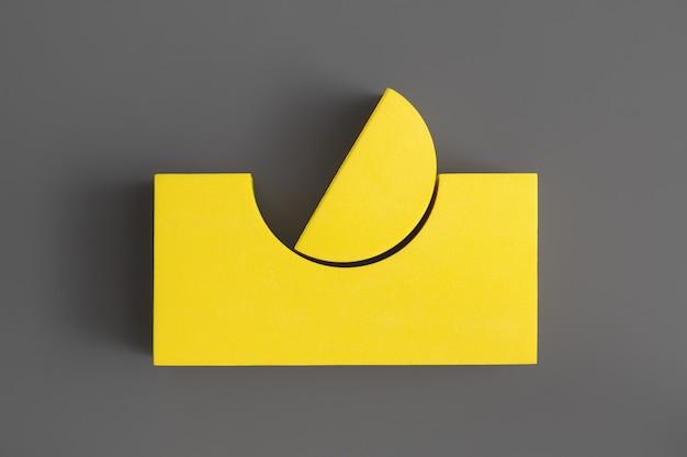 Composición laica plana de formas geométricas amarillas sobre la superficie gris definitiva. colores del año 2021. illuminating y ultimate grey. concepto de minimalismo.