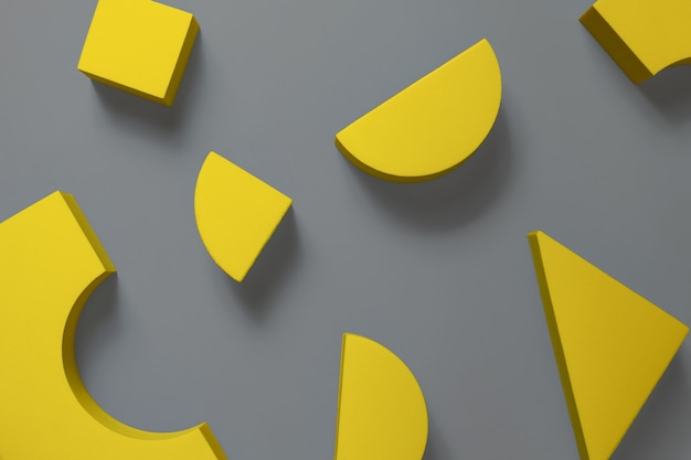Composición laica plana de formas geométricas amarillas sobre la superficie gris definitiva. colores del año 2021 Foto Premium