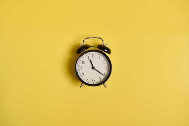 Composición laica plana de un reloj despertador, sobre fondo amarillo con espacio para texto. concepto de control de tiempo, gestión del tiempo, negocios y eventos.