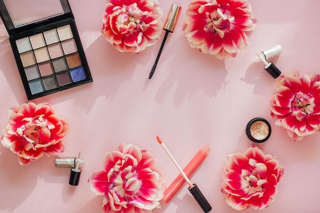 Composición laicos plana con productos para maquillaje decorativo sobre una mesa rosa. mesa de belleza