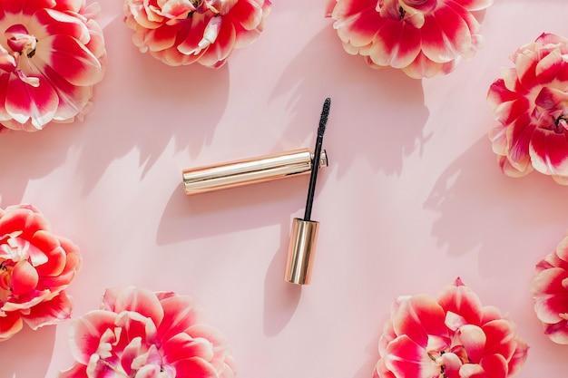 Composición laicos plana con productos para maquillaje decorativo sobre una mesa rosa. rímel y tulipán de flores sobre una mesa rosa.