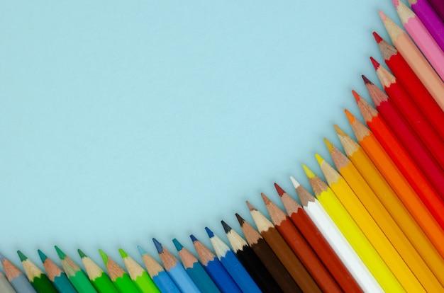 Composición de lápices de colores sobre fondo azul. endecha plana.