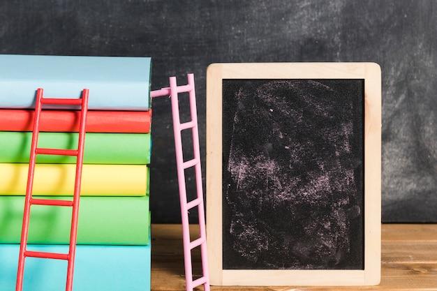 Composición de libros con escalera cerca de pizarra