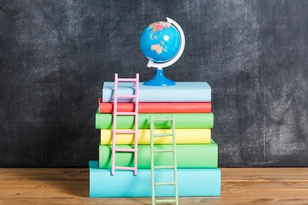 Composición de libros y globo.