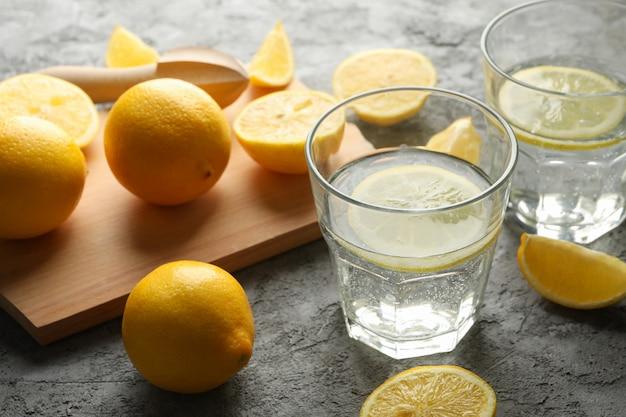 Composición con limonada y limones en mesa gris