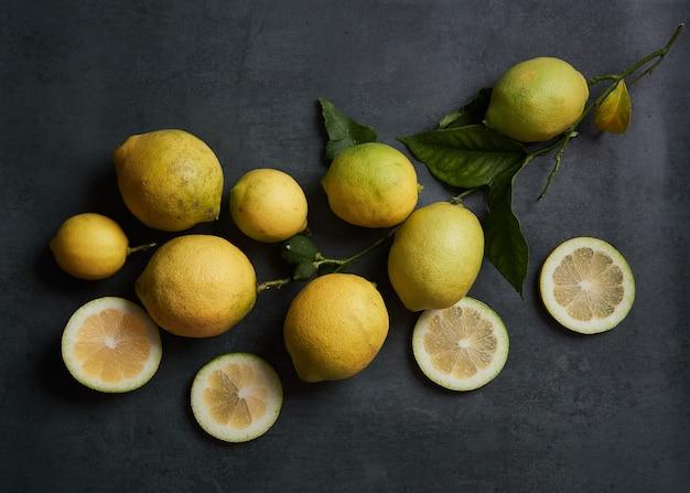 Composición de limones enteros y en rodajas con hojas y rama sobre un fondo gris