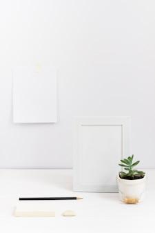 Composición del lugar de trabajo con marco blanco y jarrón de plantas.