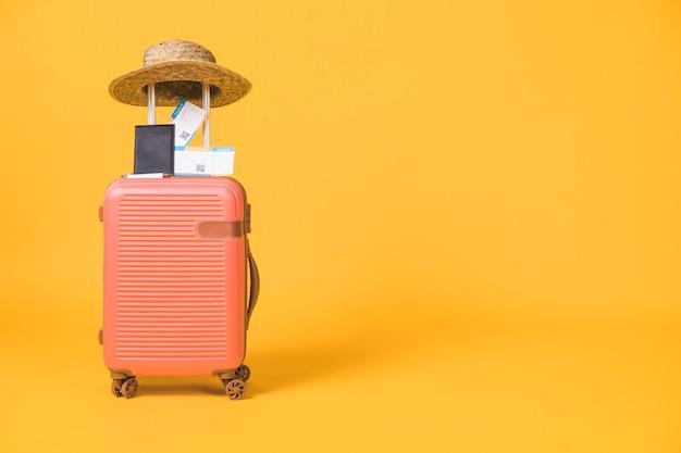 Composición de maleta y tickets de pasaporte y sombrero sobre la misma.