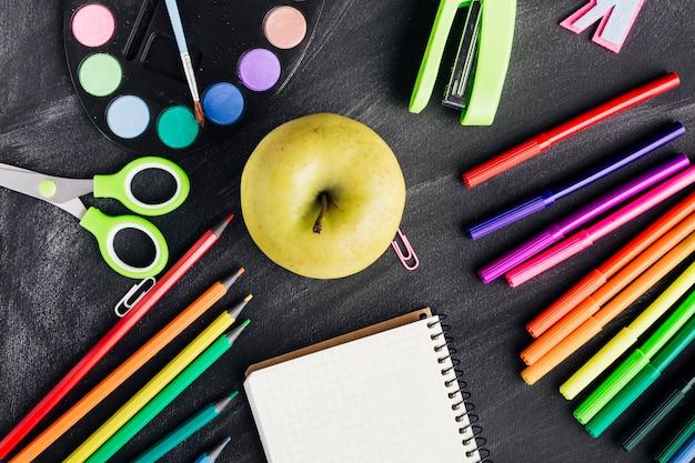 Composición con manzana y papelería.