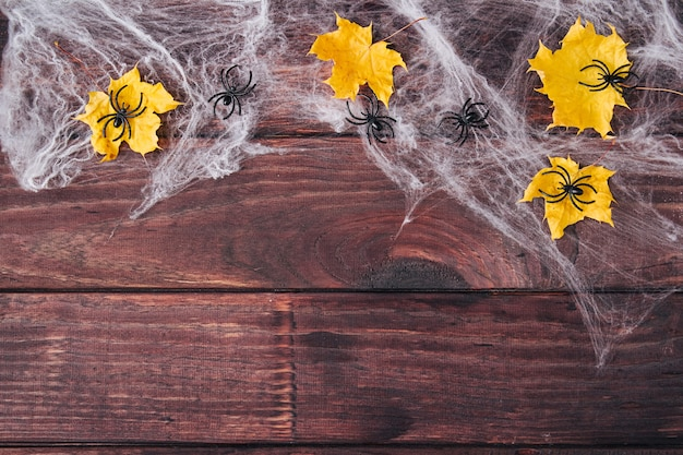 Composición del marco de halloween. hojas secas amarillas, arañas negras en la web sobre fondo de madera oscura. copie el espacio. endecha plana.