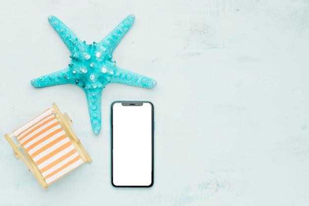 Composición marina con teléfono móvil sobre fondo claro.