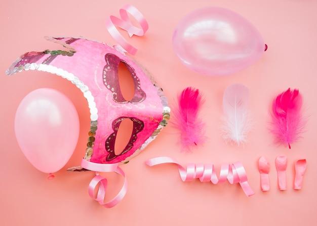 Composición de máscara cerca de globos y plumas.