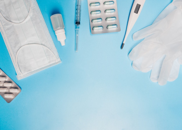 Composición con máscara médica, termómetro, jeringa, píldoras y guantes sobre un fondo azul. copyspace