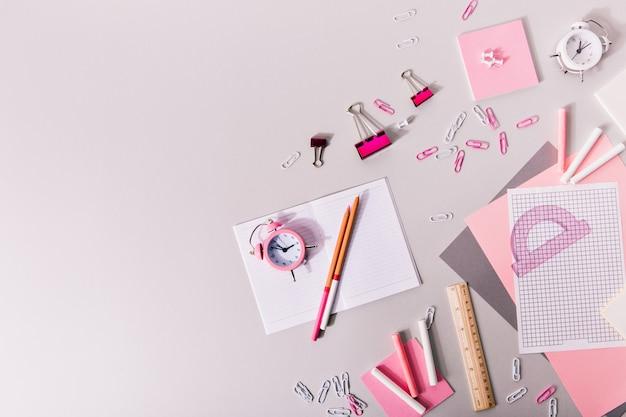 Composición de material de oficina de niña en tonos rosados y blancos.