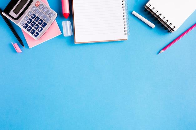 Composición de material de oficina en superficie azul.