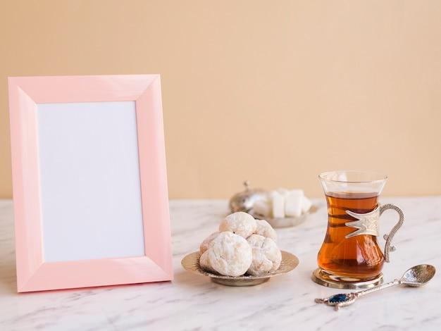 Composición de la mesa con té, pasteles y marco.