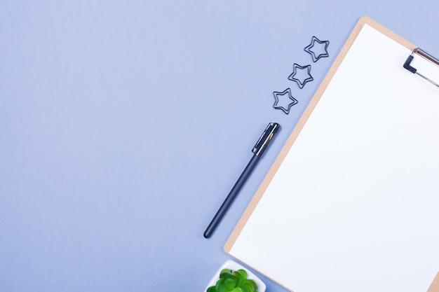 Composición mínima de escritorio con portapapeles en blanco, bolígrafo, pequeña planta en una mesa gris claro, plano, maqueta, vista superior. bosquejo. copia espacio espacio libre.