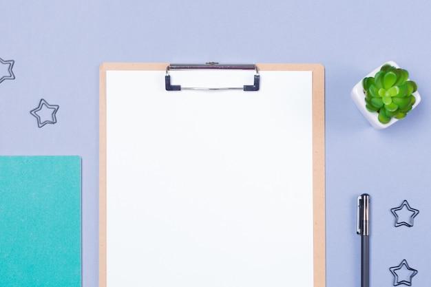 Composición mínima de escritorio con portapapeles en blanco, bolígrafo, planta pequeña y cuaderno en mesa gris claro, plano, vista superior. copia espacio espacio libre.