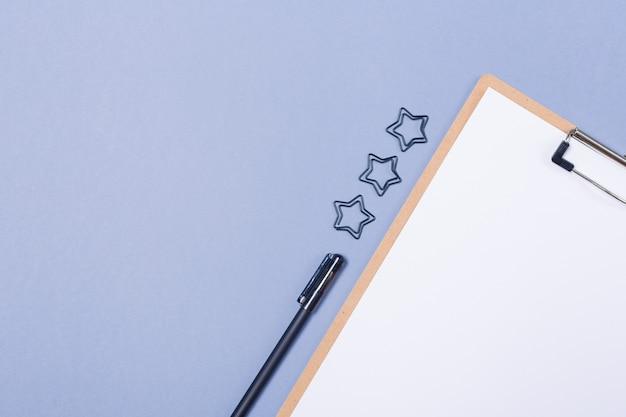 Composición mínima de escritorio con portapapeles en blanco, bolígrafo sobre una mesa gris claro, plano, vista superior. copia espacio espacio libre.