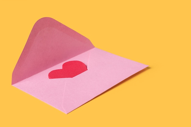 Composición mínima de un sobre rosa con corazón rojo en el interior para el día de san valentín sobre fondo amarillo