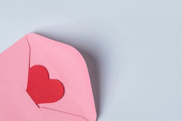 Composición mínima con un sobre rosa con corazón rojo en el interior para san valentín