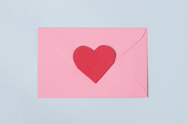 Composición mínima con un sobre rosa con corazón rojo para san valentín