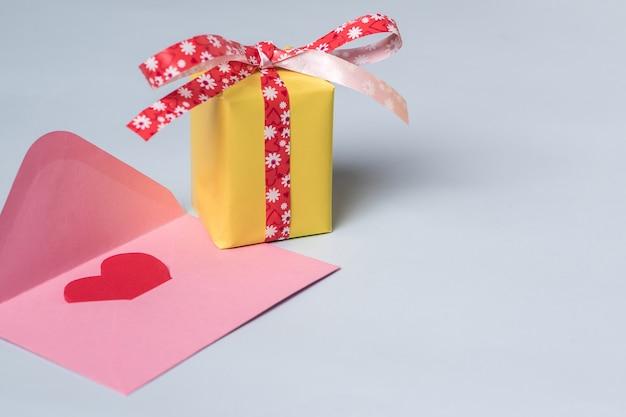 Composición mínima con un sobre rosa con corazón rojo en su interior y una caja de regalo amarilla con una cinta roja.