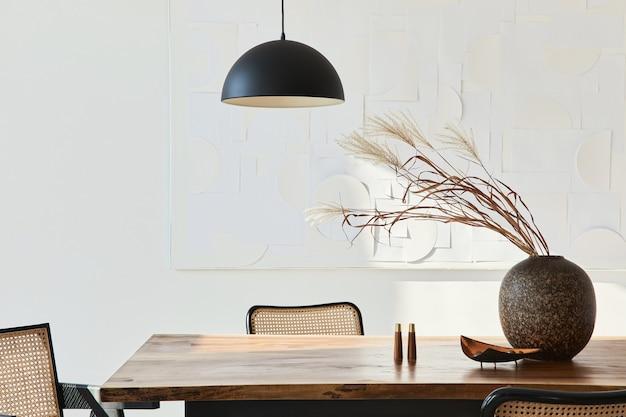 Composición minimalista del interior del comedor con mesa de madera, sillas de diseño, flores secas en un jarrón, lámpara colgante negra, cuadros de arte en la pared y elegantes accesorios personales