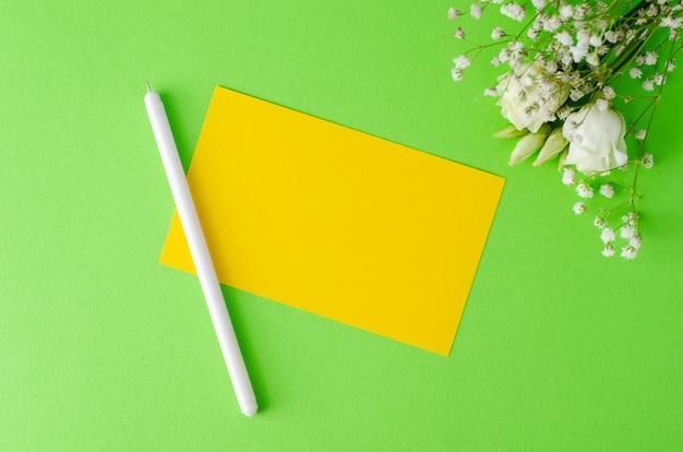Composición minimalista con una tarjeta en blanco amarilla, pluma y flores sobre fondo verde. flay laico, concepto de maqueta.