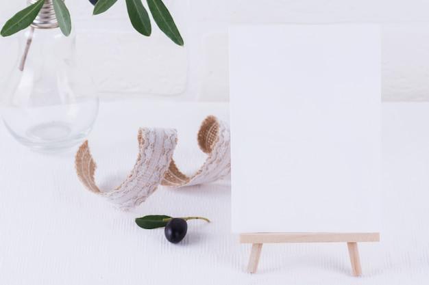 Composición minimalista con tarjeta o nota para invitación, menú en caballete