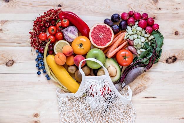 Composición moderna de frutas y verduras frescas y saludables en forma de corazón en la mesa de la cocina de madera