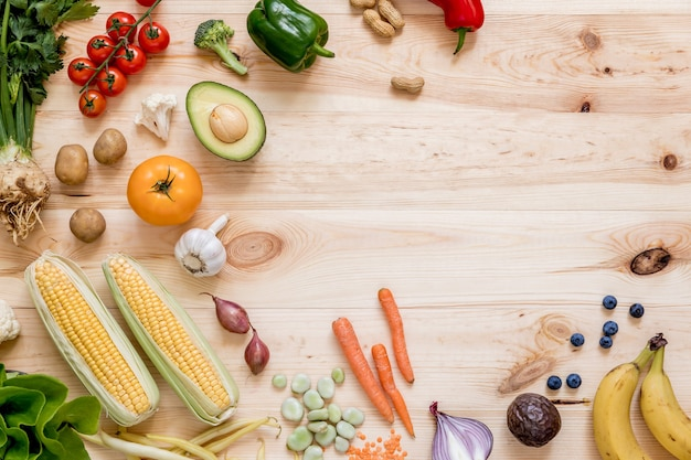 Composición moderna de frutas y verduras frescas y saludables en la mesa de madera en la cocina. fondo vegano vegetariano. cero desperdicio. vista superior. copie el espacio.