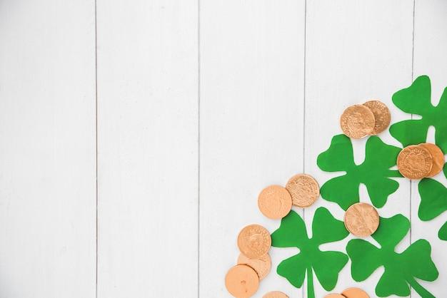 Composición de monedas y tréboles de papel verde a bordo.