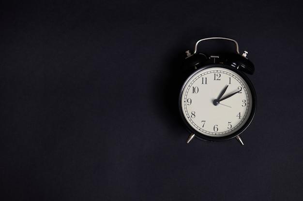 Composición monocromática laica plana con un reloj despertador vintage sobre fondo negro con espacio de copia para agregar texto. regreso a la escuela y conceptos del día del maestro, negocios, organización, gestión del tiempo, eventos