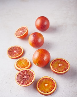 Composición de naranjas sanguinas enteras y en rodajas sobre una superficie de piedra