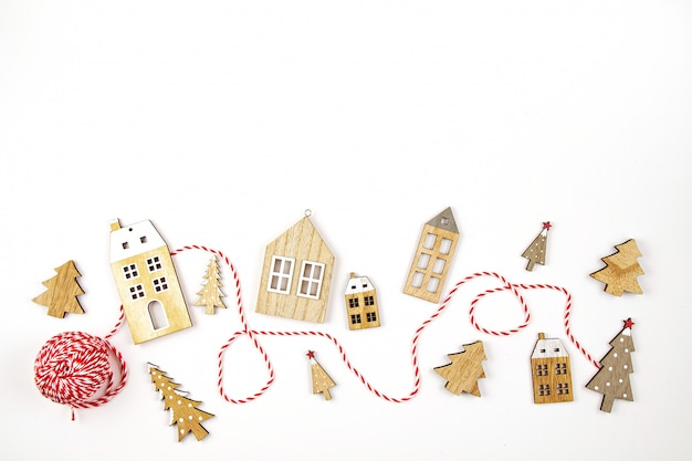 Composición de navidad con adornos de madera sobre el fondo blanco. vacaciones de temporada, tarjeta de felicitación, invitación para fiesta de navidad