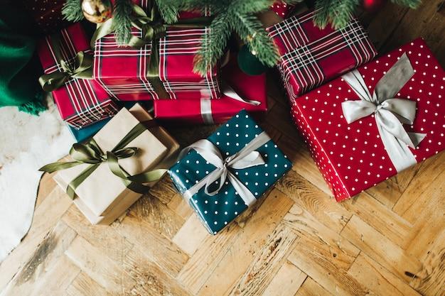 Composición de navidad año nuevo. cajas de regalo artesanales festivas envueltas en papel de colores rojo, azul y beige