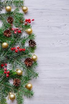 Composición de navidad con árbol de navidad y frutos rojos en mesa blanca