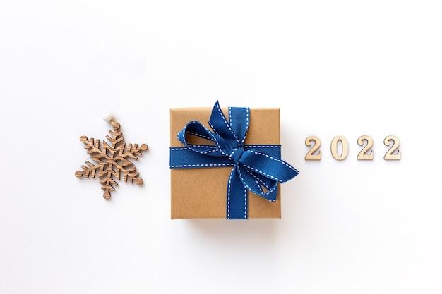 Composición de navidad con caja presente y copo de nieve de madera sobre fondo blanco feliz navidad y feliz ...