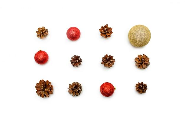 Composición de navidad conos de pino, bolas rojas y doradas sobre fondo blanco.