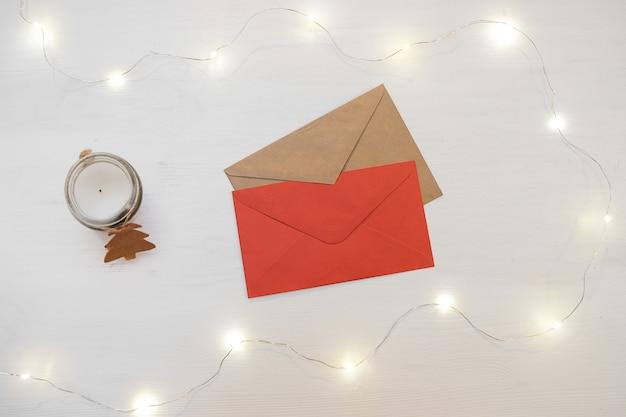 Composición de navidad decoraciones rojas con el sobre de la carta en el fondo blanco.