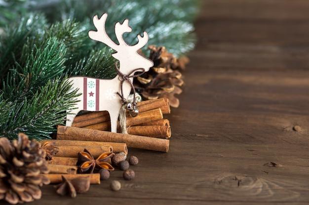 Composición de navidad con especias, ramas y renos en mesa de madera con espacio de copia de cerca