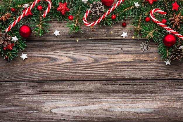 Composición de navidad y feliz año nuevo. ramas de abeto, adornos y dulces en mesa de madera