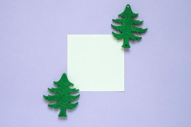 Composición de navidad con nota adhesiva y árboles de navidad