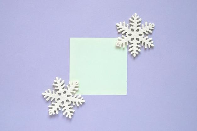 Composición de navidad con nota adhesiva y copo de nieve