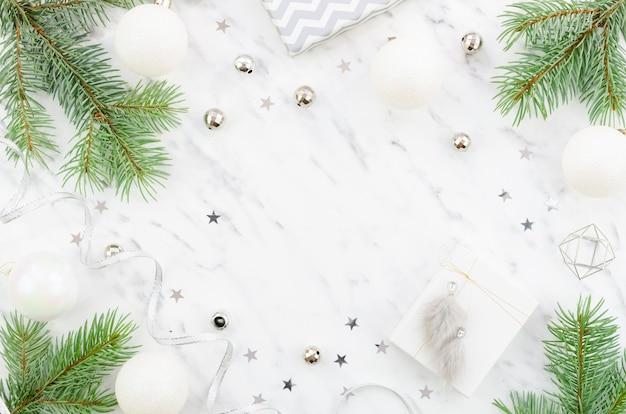 Composición de navidad o año nuevo hecha de adornos navideños plateados y ramas de abeto