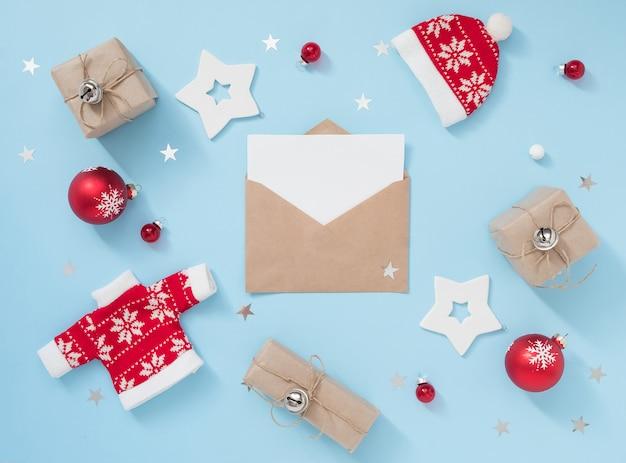 Composición de navidad o invierno con sobre y decoraciones rojas sobre fondo azul pastel. concepto de año nuevo